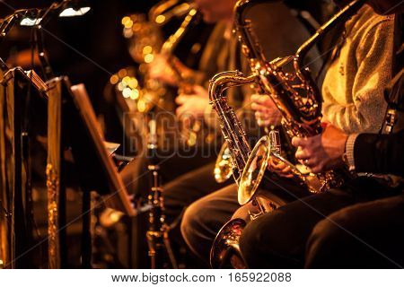 Candid view of a row of saxophone players in mid performance during a big band rehearsal.