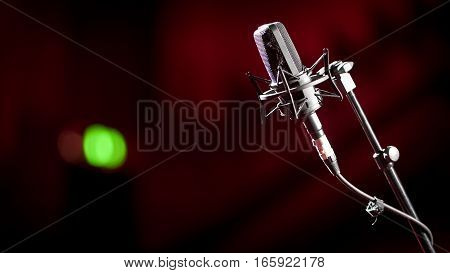 Shallow focus on a stand mounted condenser microphone with a green recording light showing in the background blur.