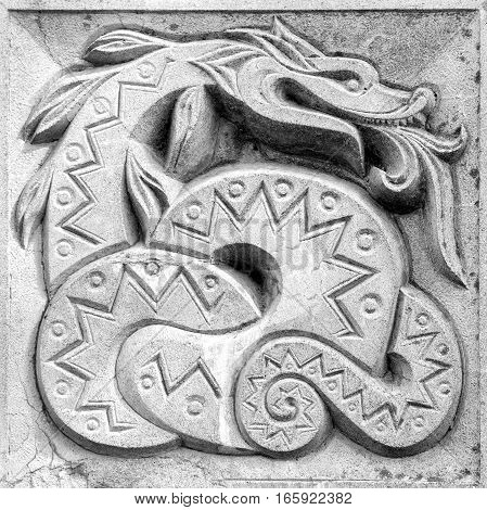 fabulous snake stone bas-relief on the wall