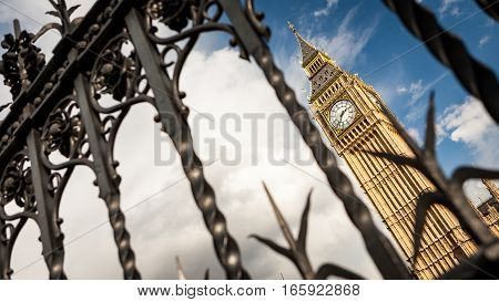 Abstract angled view of the London landmark Big Ben clock tower contained behind the railings of the Houses of Parliament the UK seat of government.