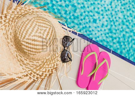 Straw Hat, Sunglasses and Flip Flops on the Poolside