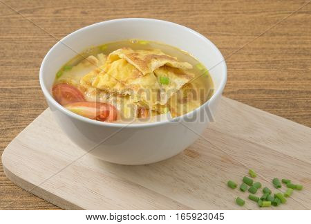 Thai Cuisine and Food Omelet Soup with Tomatoes Onion and Chopped Scallion on Wooden Cutting Board.