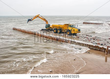 excavator loading a truck stones on the beachon cold winter day