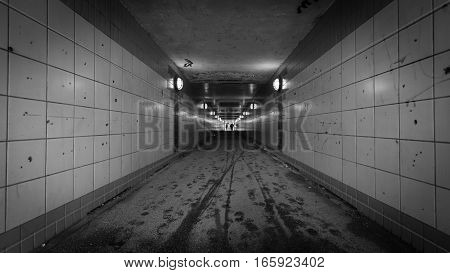 An urban pedestrian underpass with low lighting making it an intimidating location.