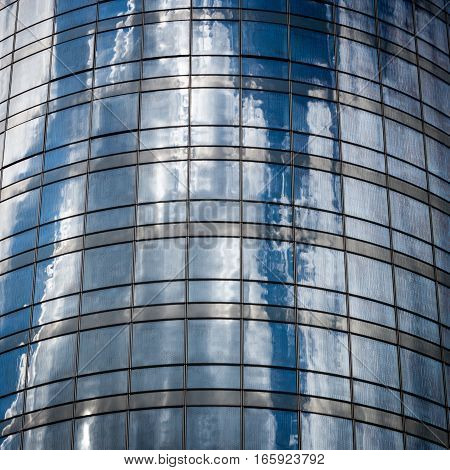 Detail of a curved cylindrical office block with a glass exterior reflecting the sky and clouds.
