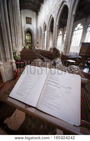 SAFFRON WALDEN UK - JUNE 8 2006: A wide-angle view of the interior of St. Mary's Church Saffron Walden Essex UK with focus on the generic religious text on an elaborate lectern.