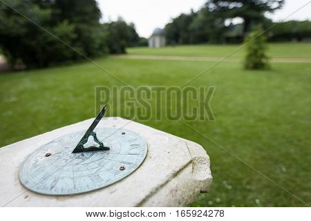 Shallow focus on a sundial in an English parkland setting.