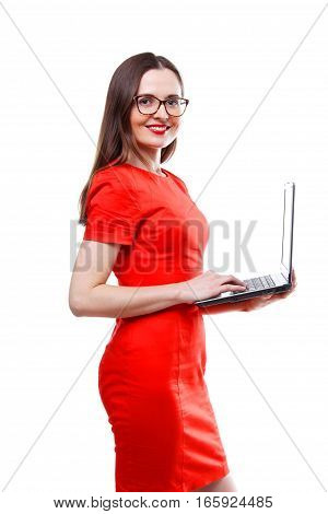 People, business, education and technology concept - standing young adult woman in red dress & glasses holding laptop computer - isolated over white background.