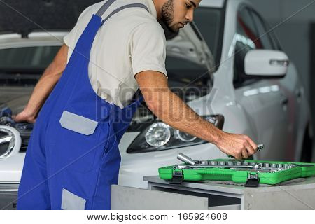 Auto Mechanic Taking a Tool while Looking at the Engine of a Car