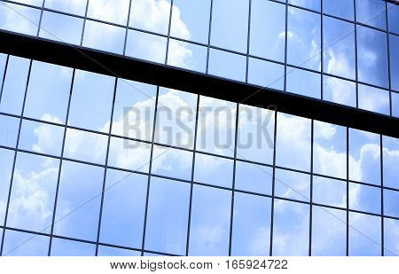 Abstract full frame office windows of an anonymous city skyscraper reflecting the blue sky and clouds.