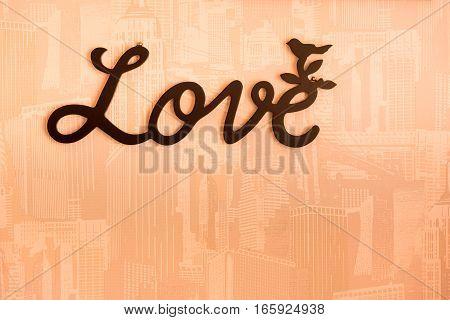 Valentine day background with word Love on orange wall background.