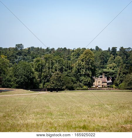 English country house surrounded by a forest and nestled in a rural countryside setting on a bright summer's day.