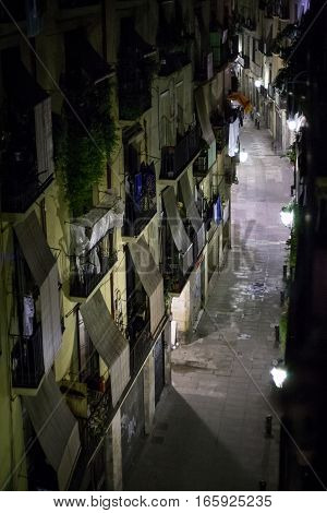 The Gothic Quarter of Barcelona, Spain, with its narrow passages and high apartment blocks. Low light ambient light with noise.