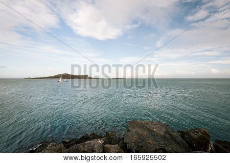 The Irish Sea from the coast near Malahide Ireland with some recreational yachts and a small island visible.