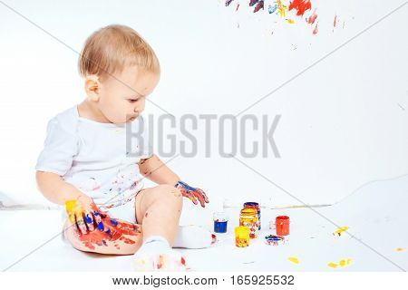 The child got dirty colors, draws on the floor