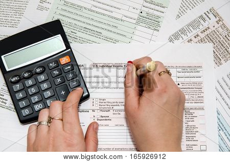Female filling out US 1040 Tax Form