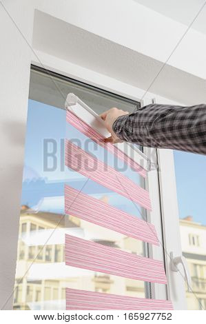Installing fabric roller blinds. A man puts rolettes to the window.