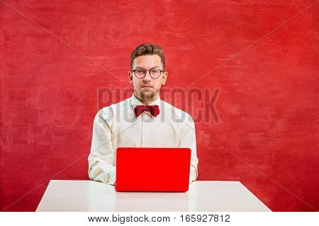 Young disappointed funny man with laptop at St. Valentine's Day on red studio background with copy space