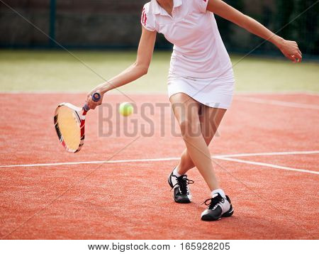 Closeup of a Female Tennis Player Hitting the Ball