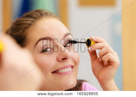 Woman Applying Black Eye Mascara To Her Eyelashes