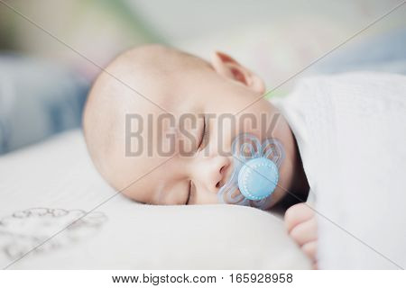Asian infant baby boy sleeping peacefully with pacifier in bedroom.