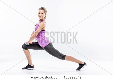 Sporty woman stretching and looking at camera on white