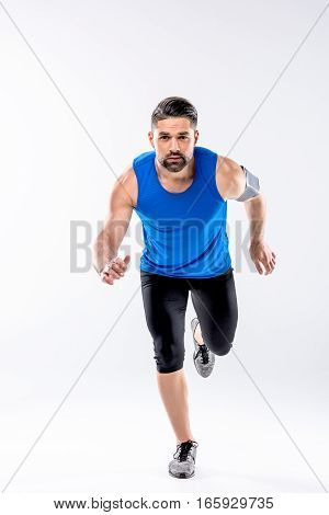Athletic man in sportswear running and looking at camera on white