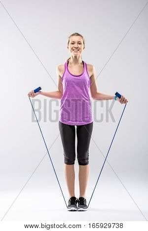 Full length portrait of smiling blonde woman exercising with skipping rope