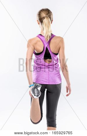 Back view of sporty blonde woman stretching on white