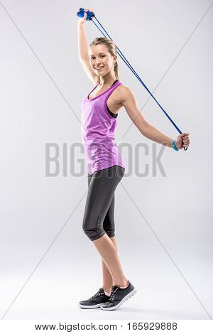 Smiling woman in sportswear exercising with skipping rope and looking at camera
