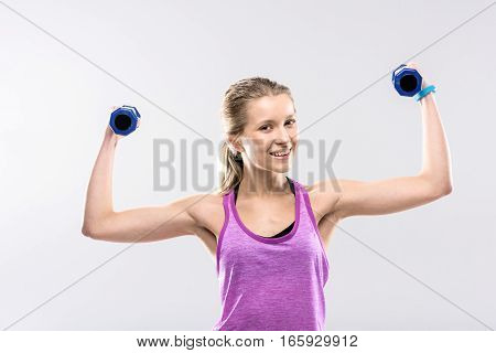 Sporty blonde woman exercising with dumbbells and looking at camera
