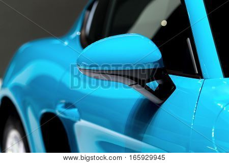 Blue side view mirror with blue modern car.