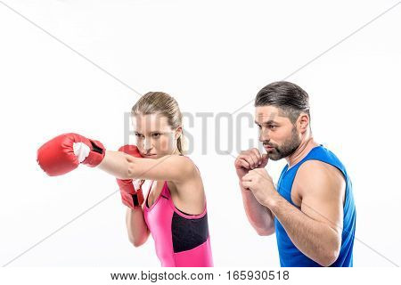 Girl practicing boxing with her personal trainer on white