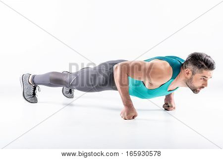 Muscular young man in sportswear doing plank exercise on fists