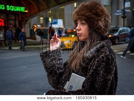 NEW YORK-JANUARY 19-A young woman smokes a cigarette while waiting to cross the street near Grand Central Terminal on January 19 2017 in New York City.