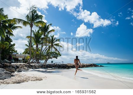 Young pretty woman with beautiful body in swimsuit running in ocean water sunny day at tropicl beach wellness concept