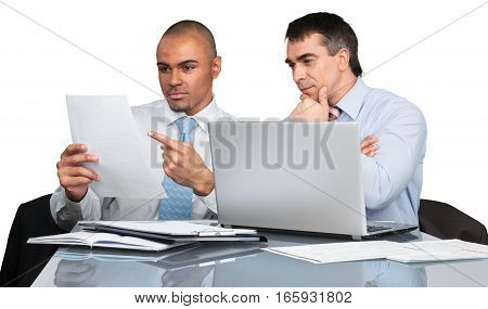 Businessmen reviewing documents and working on a laptop