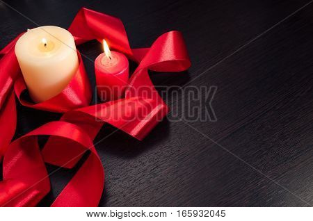Burning candles, wrapped in red ribbon. Gift for Valentine's Day. Dark texture with a romantic symbol of love by fourteen february.