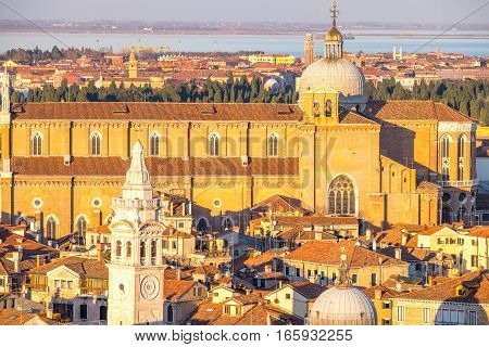 Aerial view of Venice, Italy, at sunset with rooftops of buildings and warm sunlight at sunset.