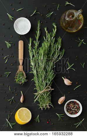 Bunch of rosemary with garlic olive oil and spices on black wooden background. Artistic Still Life
