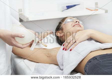 Beautician Giving Epilation Laser Treatment To Woman On