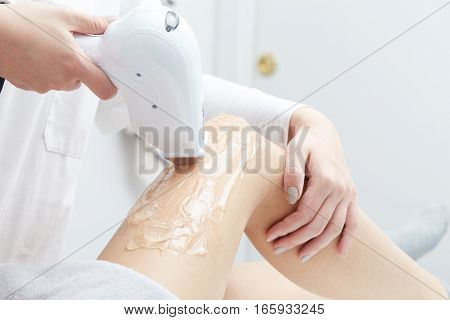 Beautician Giving Epilation Laser Treatment To Woman On Thigh