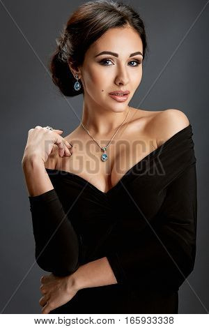 Beautiful woman standing in a black dress over gray background. Woman looking at the camera