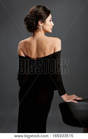 Beautiful woman standing in a black dress over gray background. A woman is standing back.