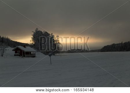 wooden house in snow valley on sunset background in Levi, Finland
