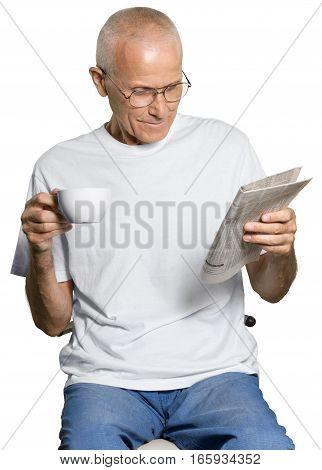 Portrait of a Senior Man Holding a Mug while Reading Newspaper