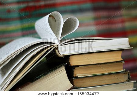 Opened book with heart shaped pages on colourful background, concept valentine's day