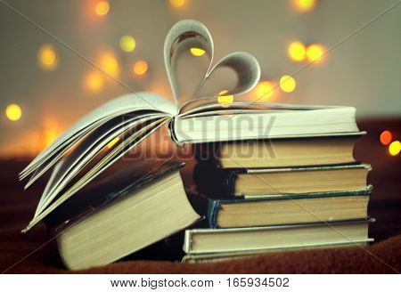 Opened book with heart shaped pages with lights glowing background, concept valentine's day