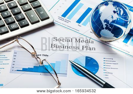 Glass Globe, Pen and Calculator on Business Plan
