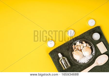 Spa set: soap, essential oil, sea salt and towel on a yellow background. Still life. Copy space